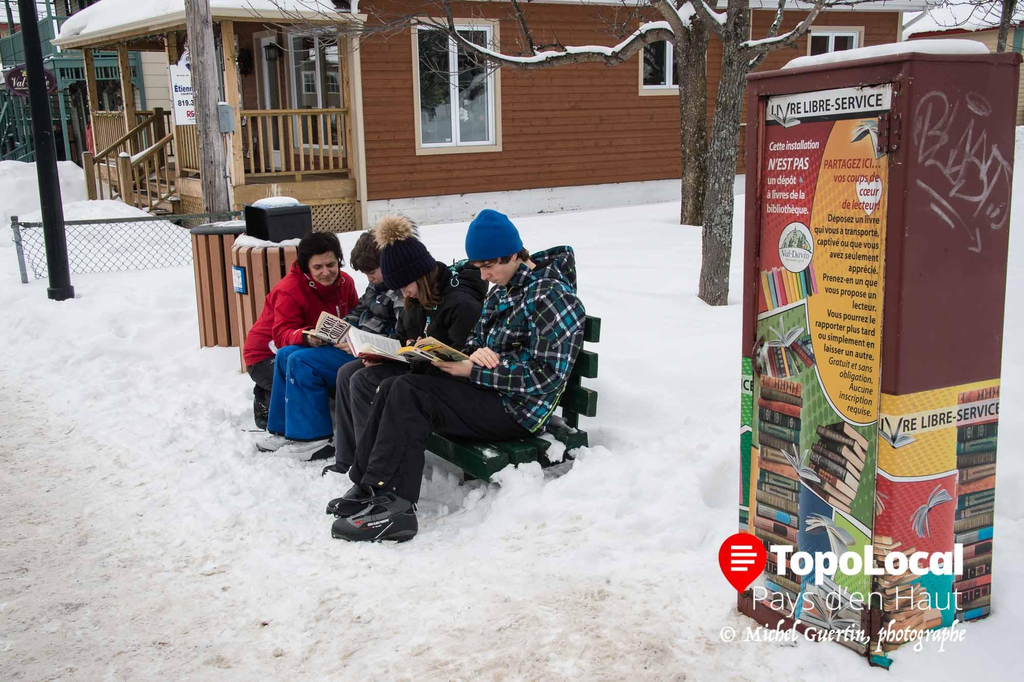 Ces jeunes en compagnie de leur mère prennent du temps pour lire un des livres mis à leur disposition gratuitement en accès libre sur la rue de l'Église à Val-David.