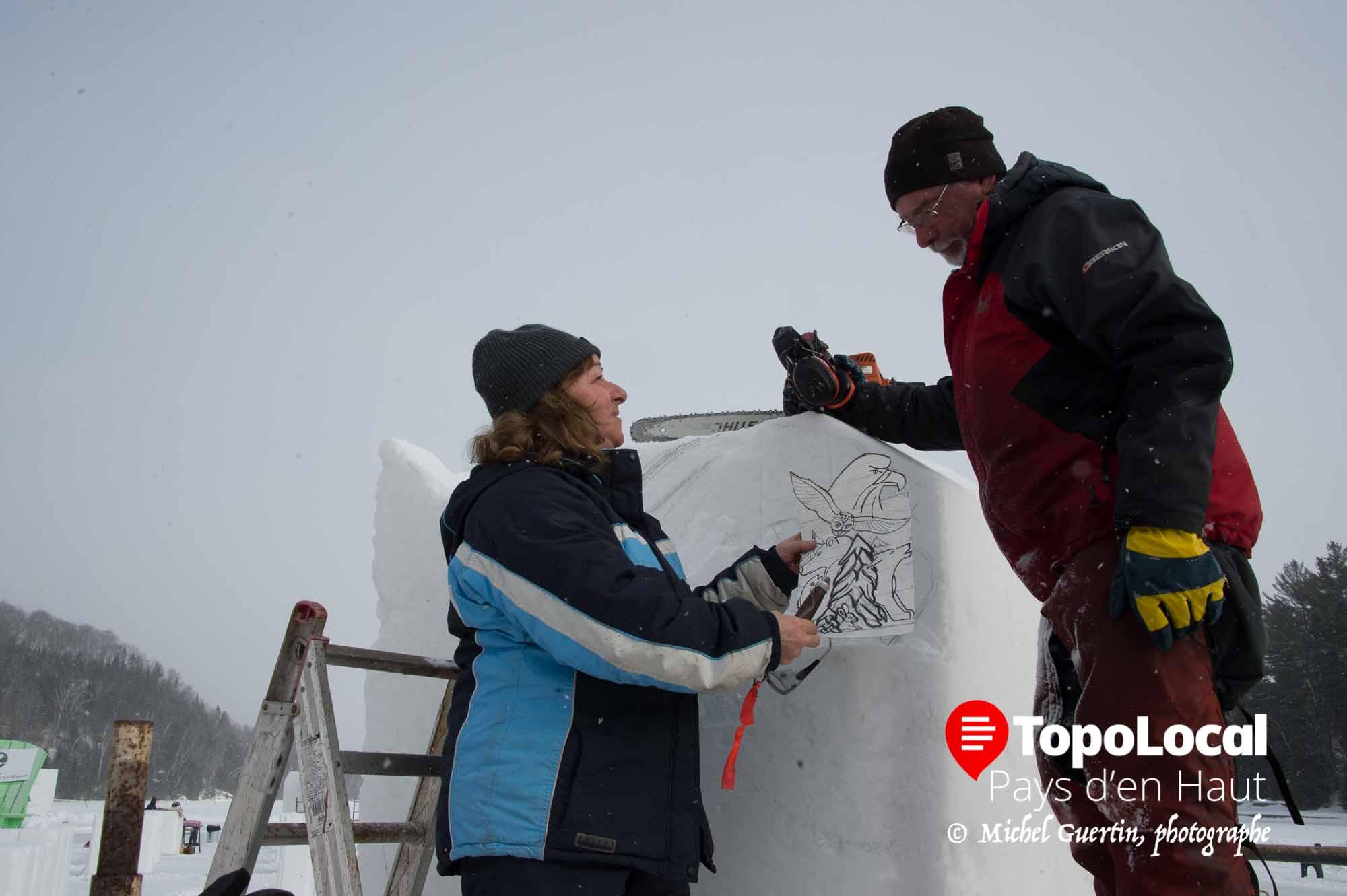 Les artistes sculpteurs sur neige Micheline Coutlé et Pierre Turgeon se consultent avant de commencer à créer leur sculpture.