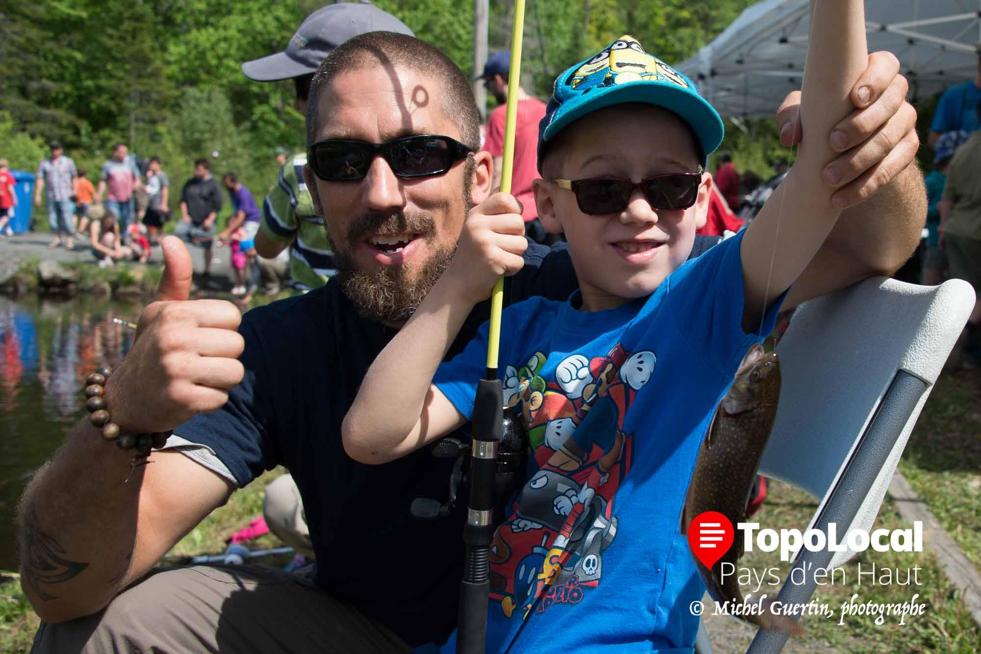 Sourires d'un papa et de son jeune garçon qui vient de prendre sa première truite à vie.