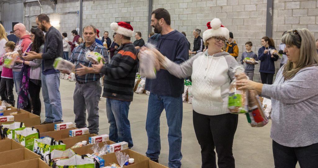 Les bénévoles chantent, jasent, dansent et s'amusent ferme au son de la musique de Noël, tout en remplissant des centaines de paniers de Noël qui seront distribués aux personnes dans le besoin.