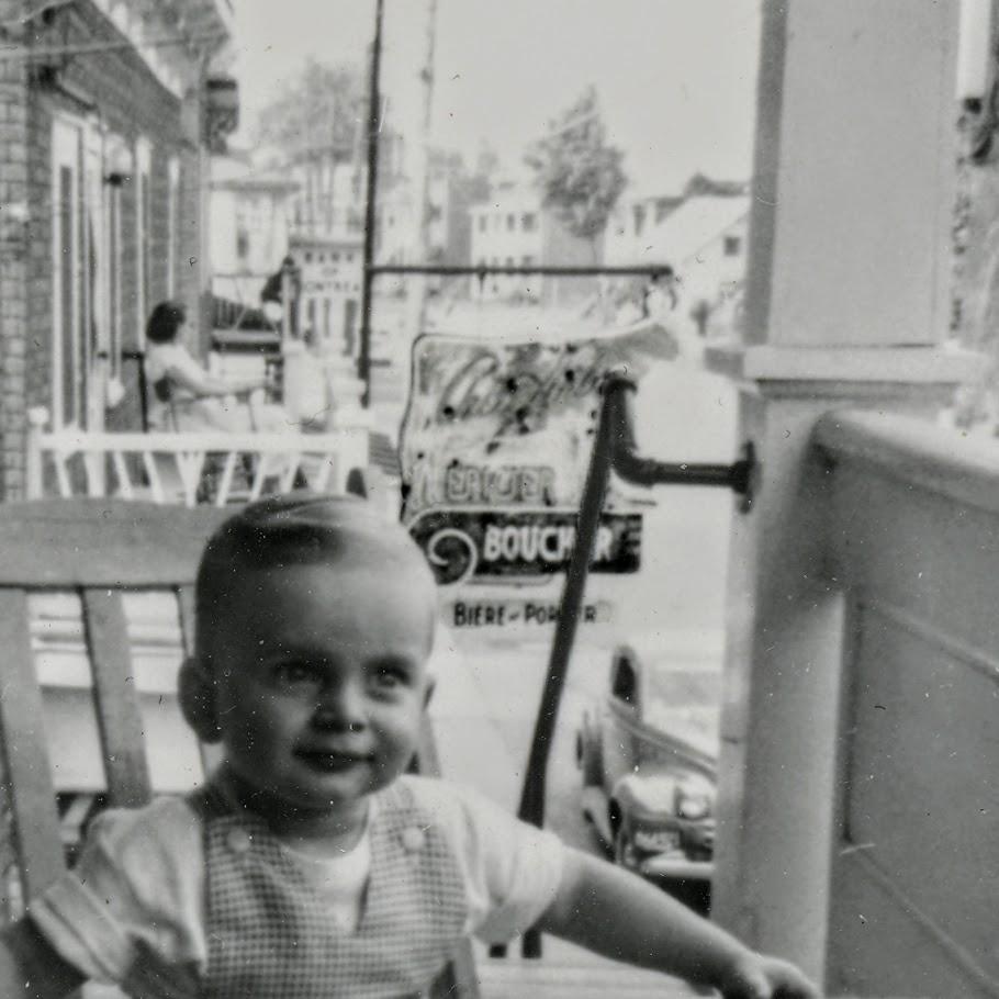 Derrière l'enfant, l'affiche en forme de vache de l'épicerie au-dessus de laquelle habitait Mme Dupont.